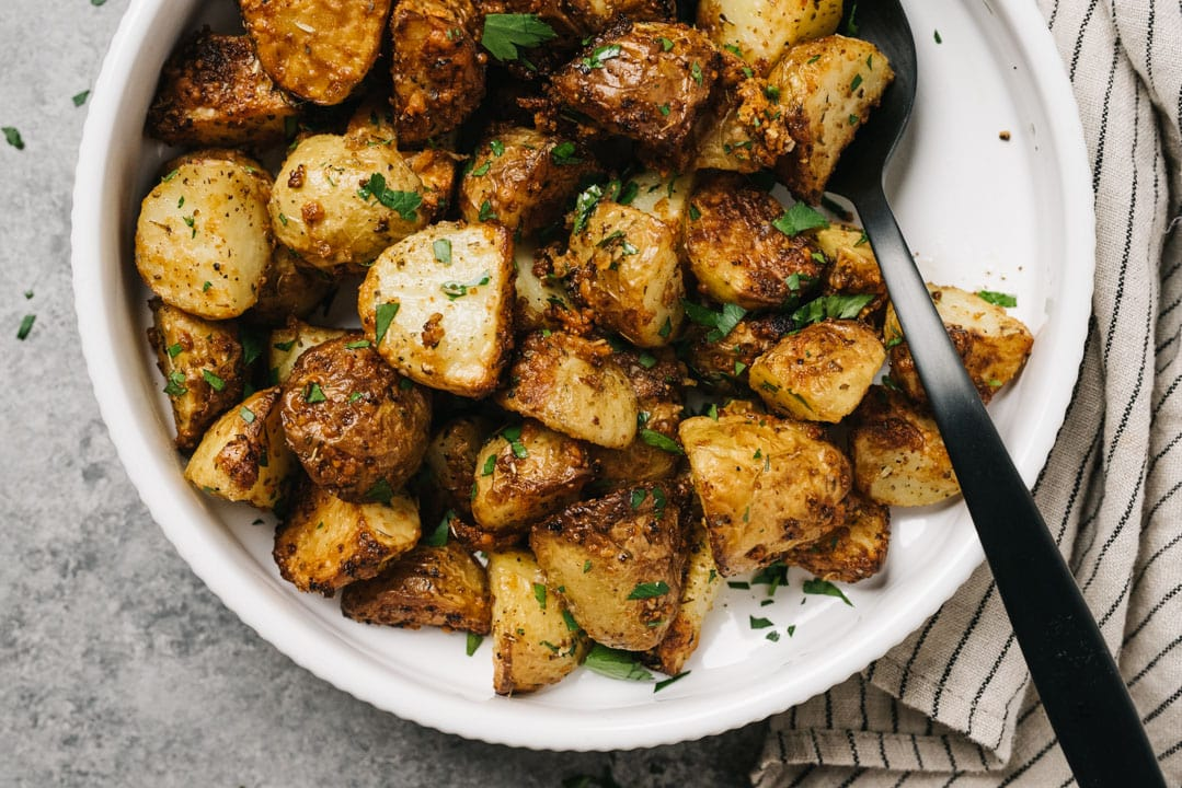A bowl of air fryer potatoes in a white serving bowl with a black serving spoon and striped linen napkin.