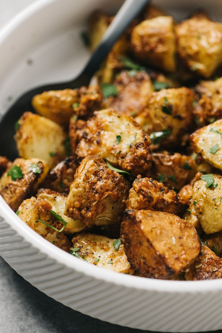 Side view, garlic parmesan air fryer potatoes in a white serving bowl, garnished with parsley.