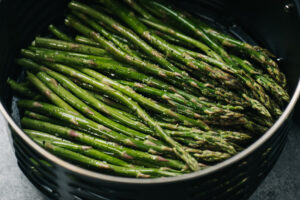 Side view, asparagus spears tossed with olive oil, salt, and pepper in the basket of an air fryer.