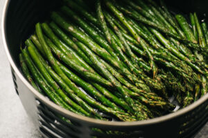Side view, cooked asparagus spears in the basket of an air fryer.