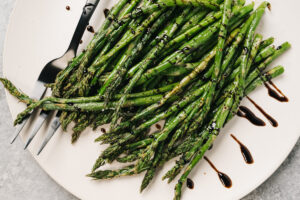 Air fryer asparagus spears on a cream platter, drizzled with balsamic reduction, with a silver serving fork on a concrete background.