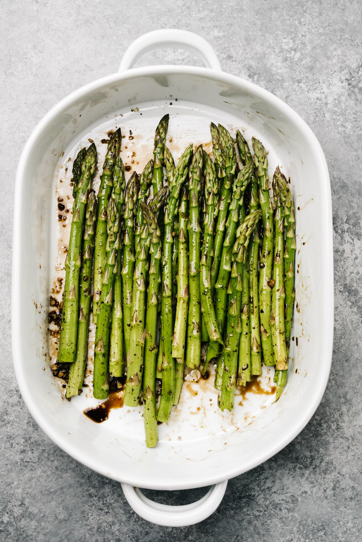 Asparagus spears in a casserole dish with olive oil, balsamic vinegar, salt, and pepper.