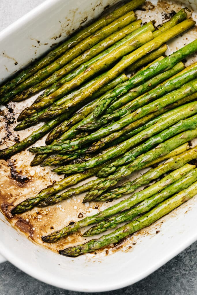 Balsamic baked asparagus spears in a casserole dish.