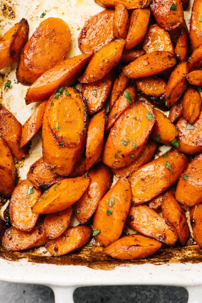 Honey baked carrots in a casserole dish, garnished with finely chopped parsley.