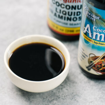 A small bowl filled with coconut aminos on a concrete background with two bottles of coconut aminos in the background.