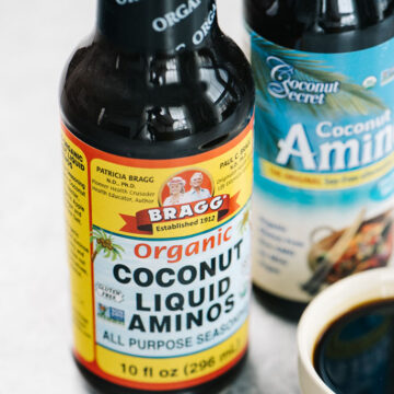 Two bottles of coconut aminos on a concrete background with a small dish of coconut aminos to show texture and color.