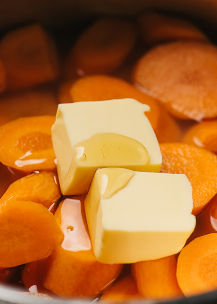 Sliced carrots tossed with water, cornstarch, butter, and honey in a small saucepan.