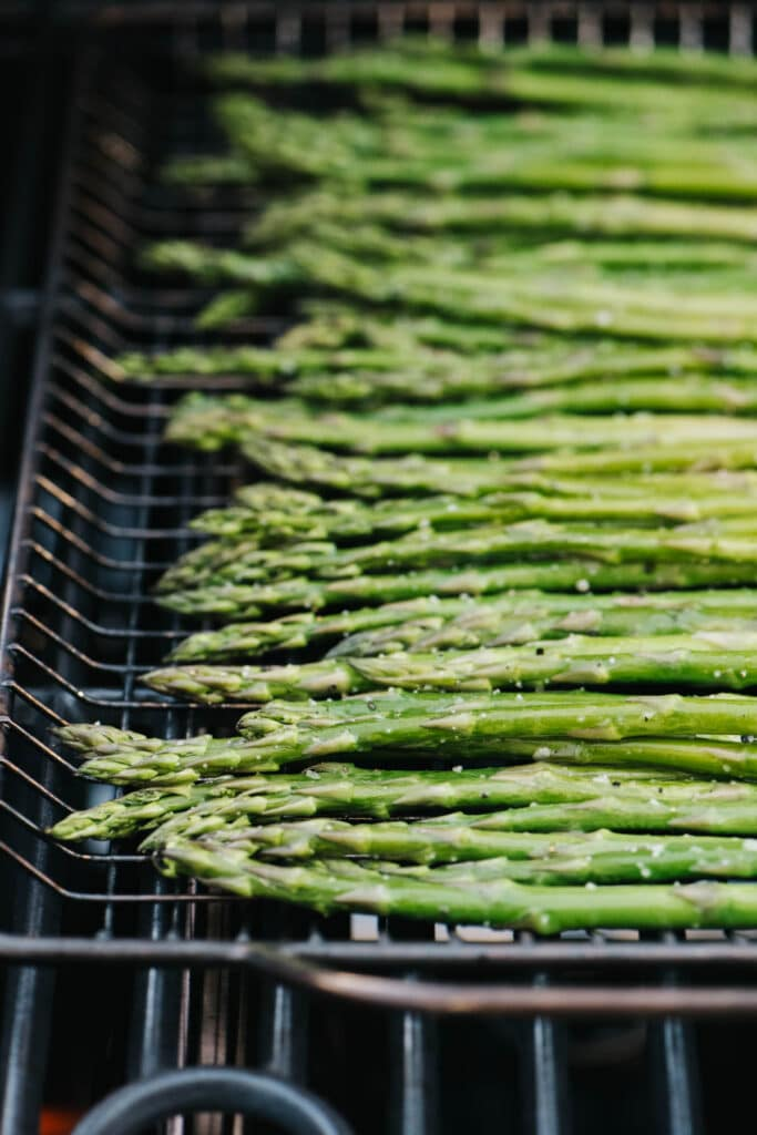 Asparagus spears over a grilling basket on a grill.