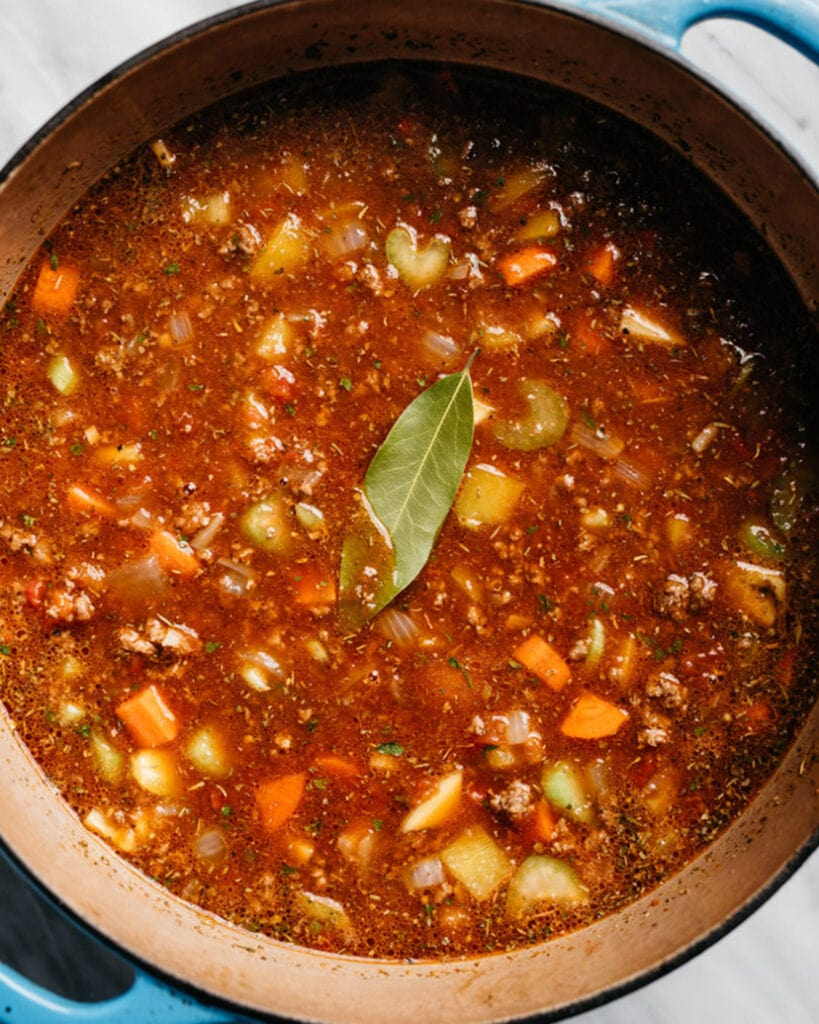 Hamburger soup with vegetables and potatoes in a blue soup pot before simmering.
