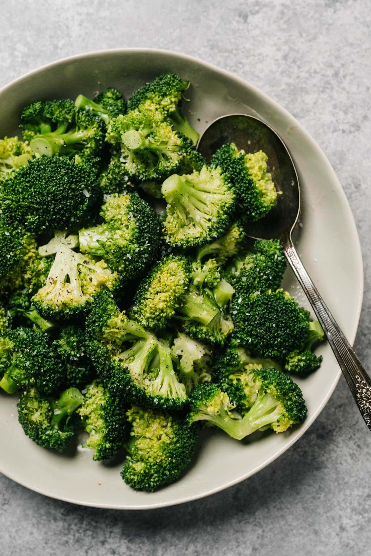 Steamed broccoli in a tan serving bowl with a silver serving spoon on a concrete background.