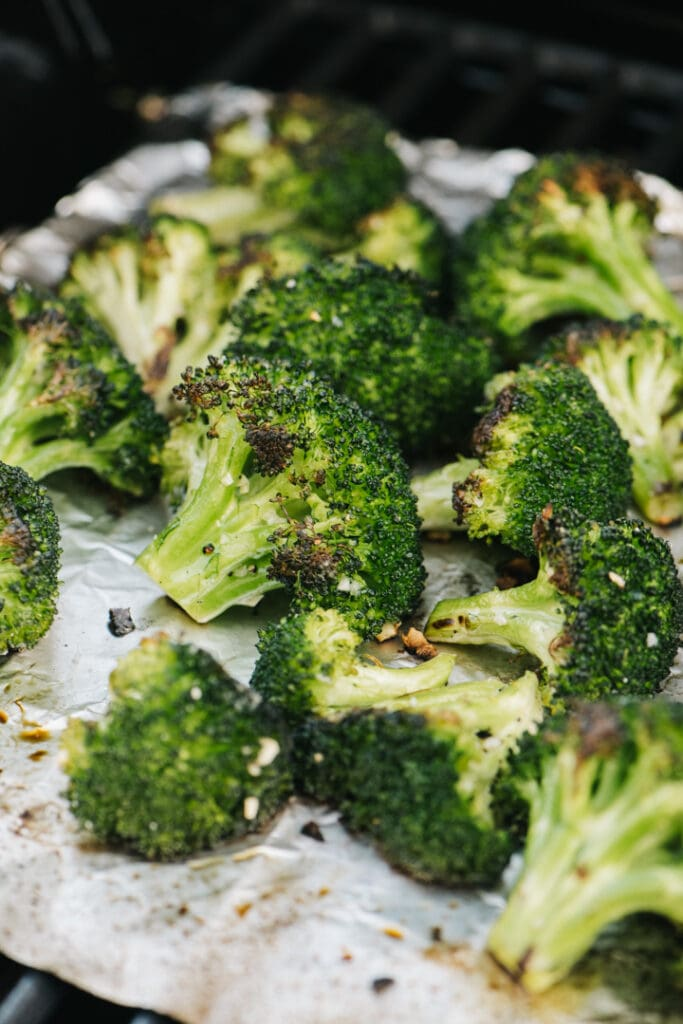 Side view, grilled broccoli florets on a piece of foil over a grill grate.