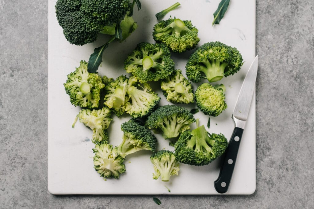 A head of broccoli trimmed down to florets on a cutting board with a paring knife.