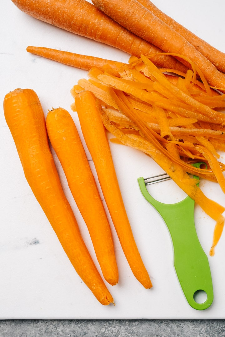 Three carrots on a cutting board, skins shaved with a vegetable peeler.