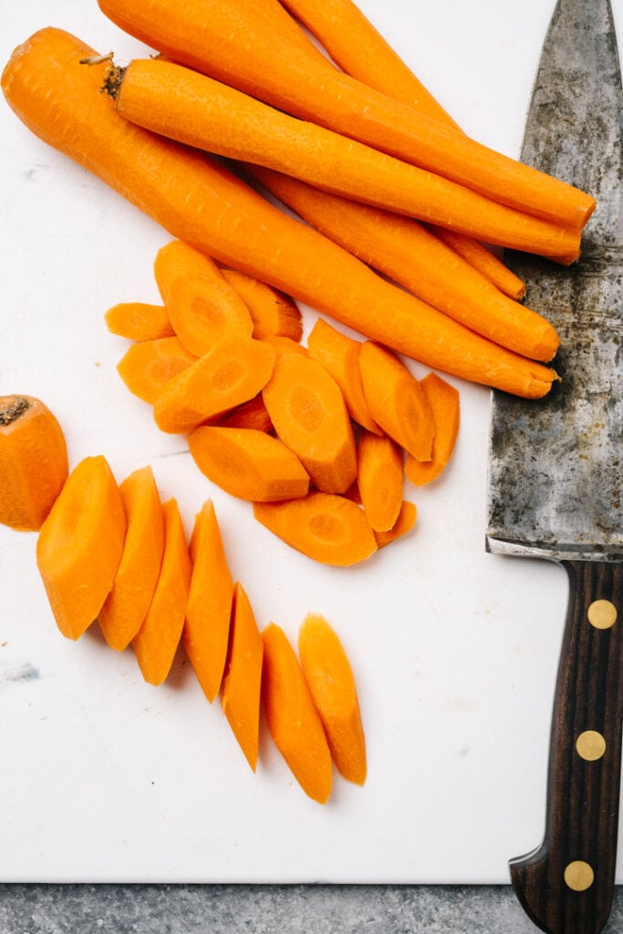 Cutting carrots at an oblique angle on a white cutting board with a large chef's knife.