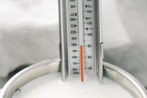 A thermometer in a pot of milk showing a temperature of 180°F.