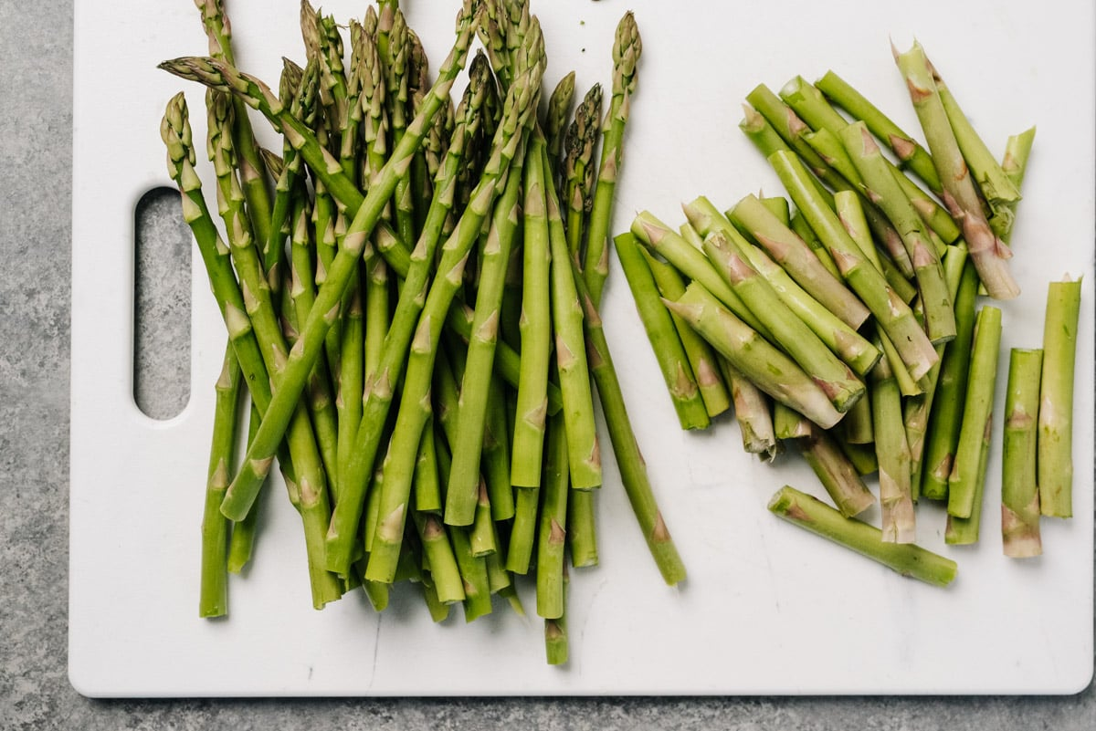 Trimmed asparagus spears on a white cutting board.