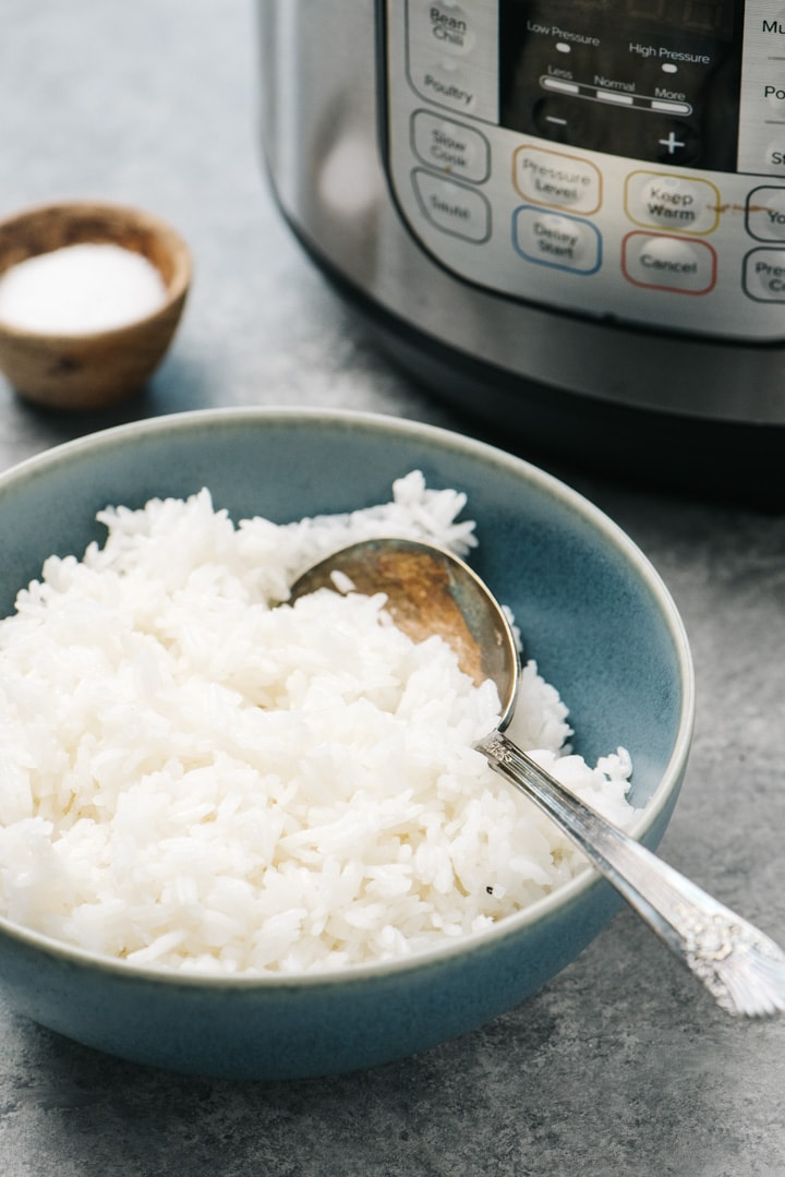 Side view, a blue bowl of jasmine rice with an instant pot in the background.