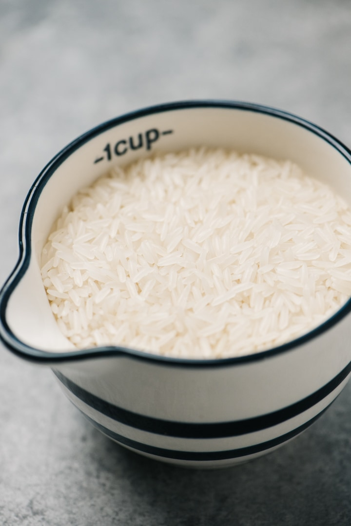 Jasmine rice in a 1-cup measuring cup.
