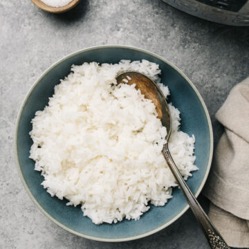 A blue serving bowl of instant pot jasmine rice with a pressure cooker off to the side and a tan linen napkin.