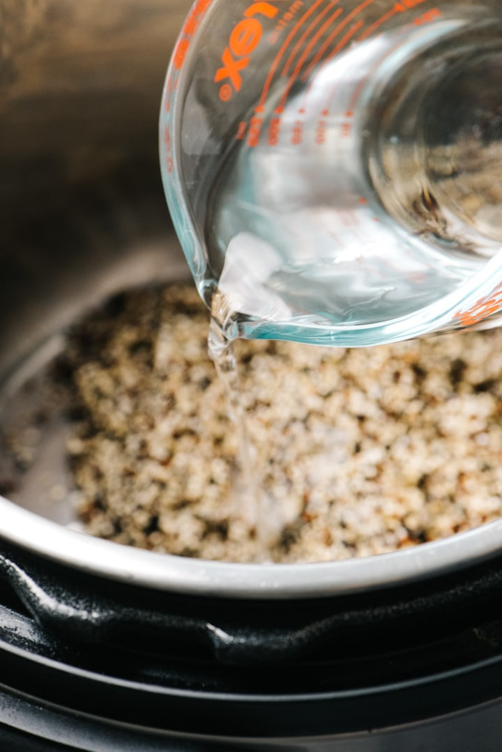 Pouring water into an instant pot with quinoa, salt, and olive oil.