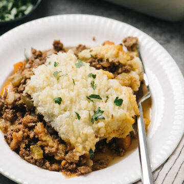 Side view, a serving of Keto Shepherd's Pie on a white plate with a fork with a casserole dish in the background.