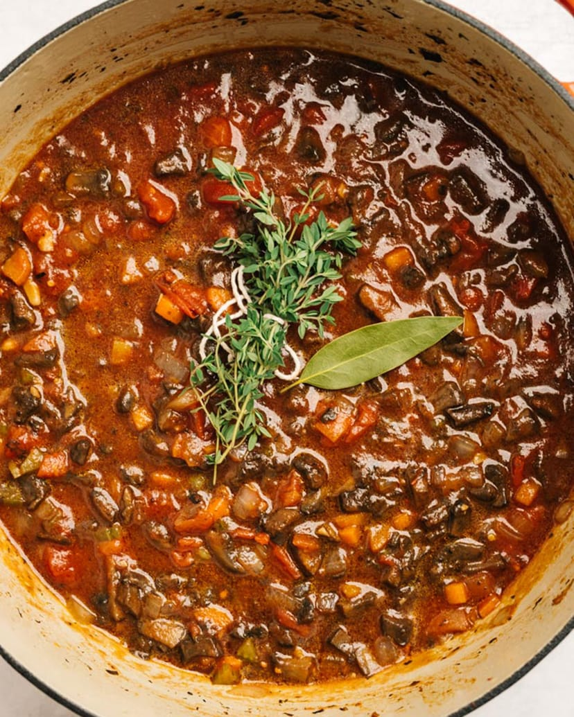 Mushroom bolognese topped with fresh thyme and a bay leaf in a soup pot before simmering.