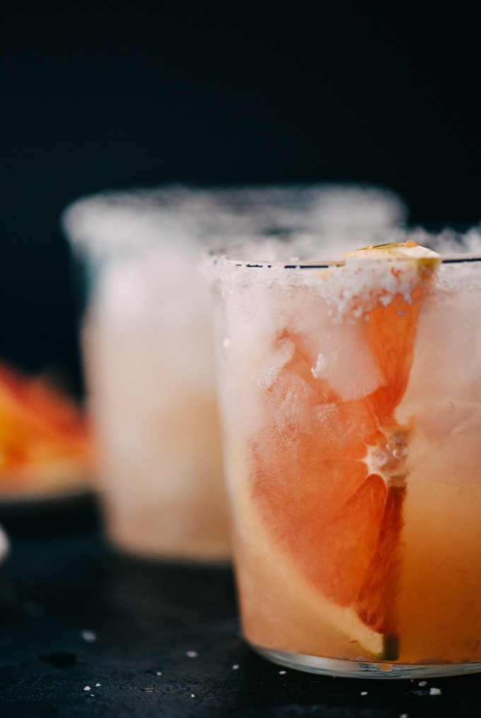 Two paloma drinks with salted rims and grapefruit slices on a chalkboard background.