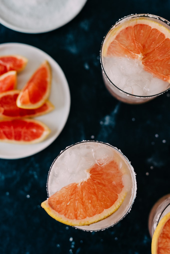 From overhead, paloma cocktails on a table with a small plate of grapefruit wedges and a shallow dish of salt.