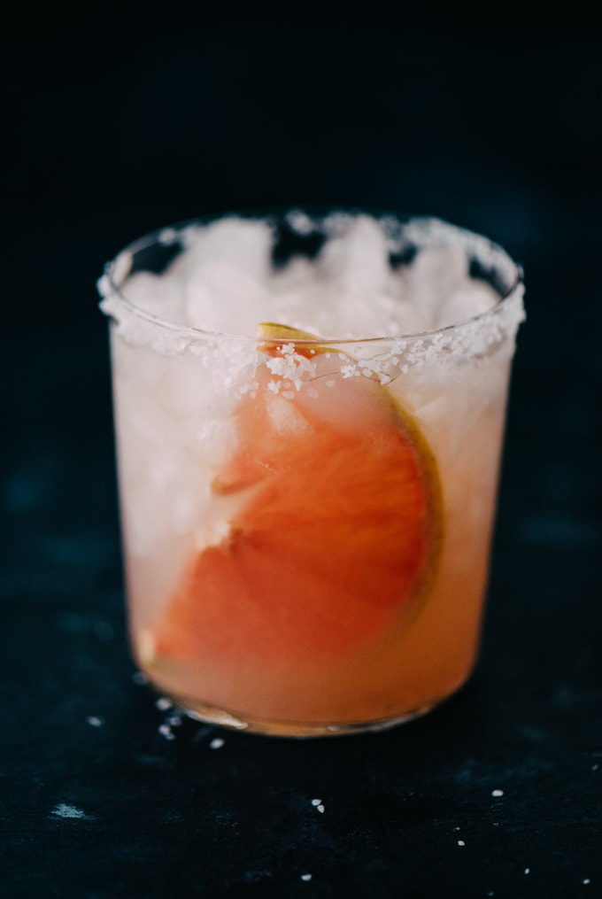 A paloma cocktail with a salted rim and grapefruit slice on a chalkboard background.