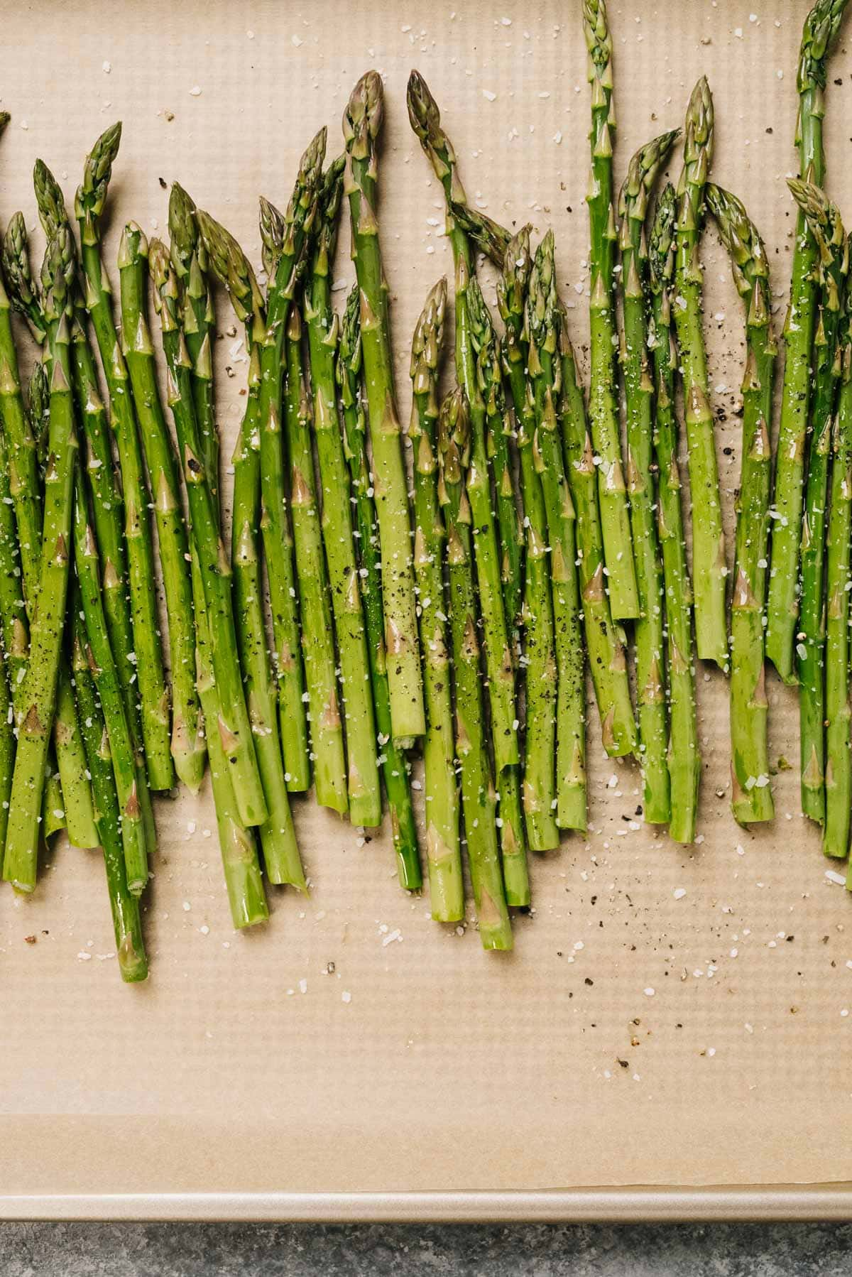 Asparagus spears tossed with olive oil, salt, and pepper on a parchment lined baking sheet.