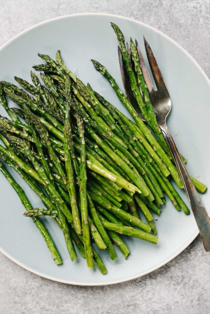 Roasted asparagus on a blue plate with a serving fork.