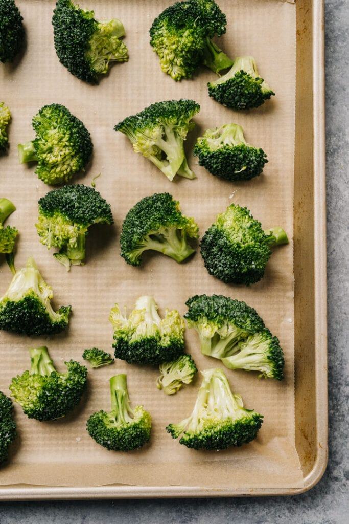 Broccoli florets tossed with olive oil in salt arranged in a single layer on a parchment lined baking sheet.