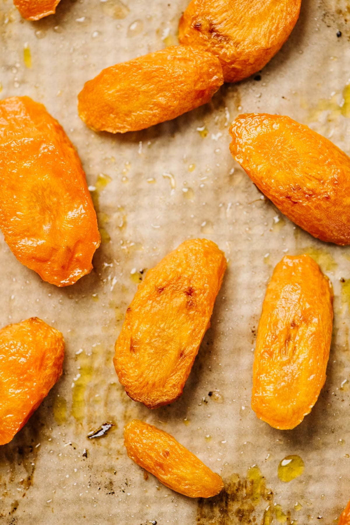 Sliced roasted carrots on a parchment lined baking sheet.