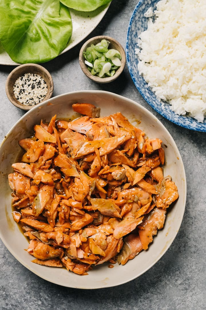Flaked salmon in a bowl tossed with teriyaki sauce surrounded by bowls of fixings for lettuce wraps (butter lettuce, steamed rice, sesame seeds, and green onions).