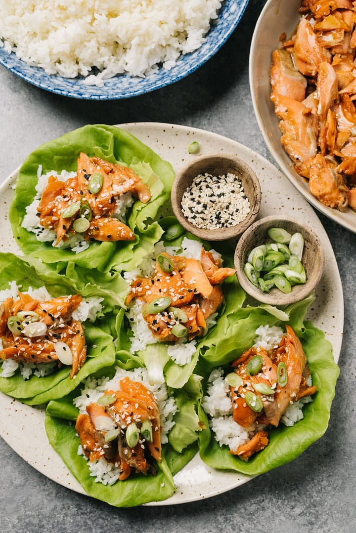 A platter of salmon lettuce wraps with two serving bowls of teriyaki salmon and steamed rice.