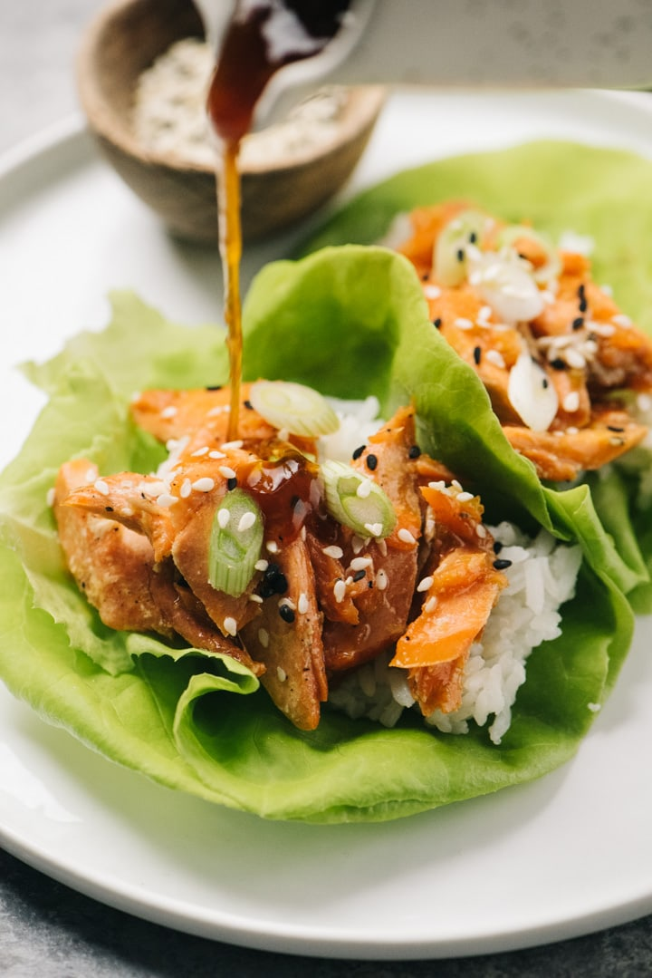 Drizzling teriyaki sauce onto a salmon lettuce wrap.