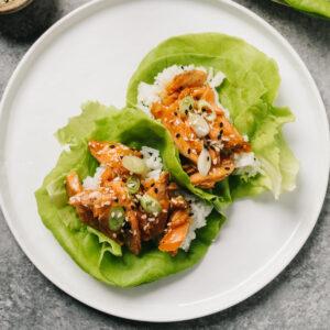 Two teriyaki salmon wraps on a white plate.