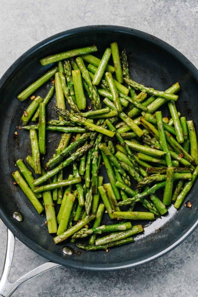 Chopped asparagus sautéing in a skillet.