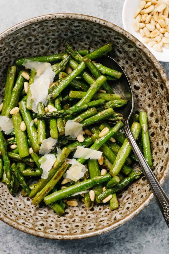 Sautéed asparagus in a brown speckled bowl with toasted pine nuts and shaved parmesan cheese.