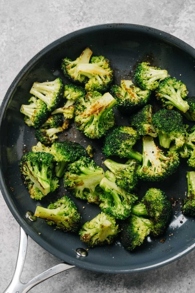 From overhead, sautéed broccoli in a skillet with olive oil and garlic.