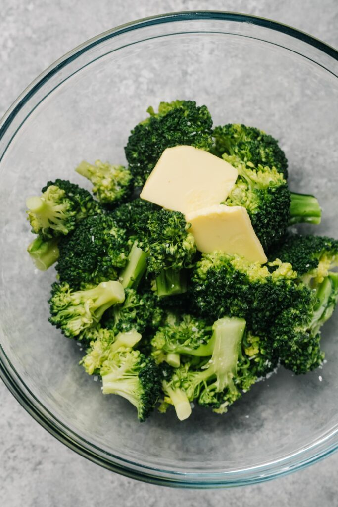 Two pats of butter melting over steamed broccoli in a glass bowl.
