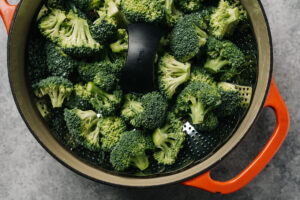 Broccoli florets in a steamed basket positioned in a dutch oven.