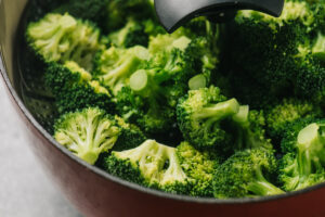 Side view, steamed broccoli florets in a steamed basket positioned in a dutch oven.
