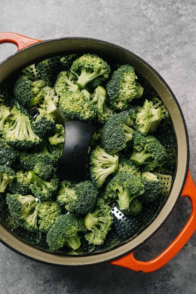 Raw broccoli florets in a steamed basket fitted into a dutch oven pot.