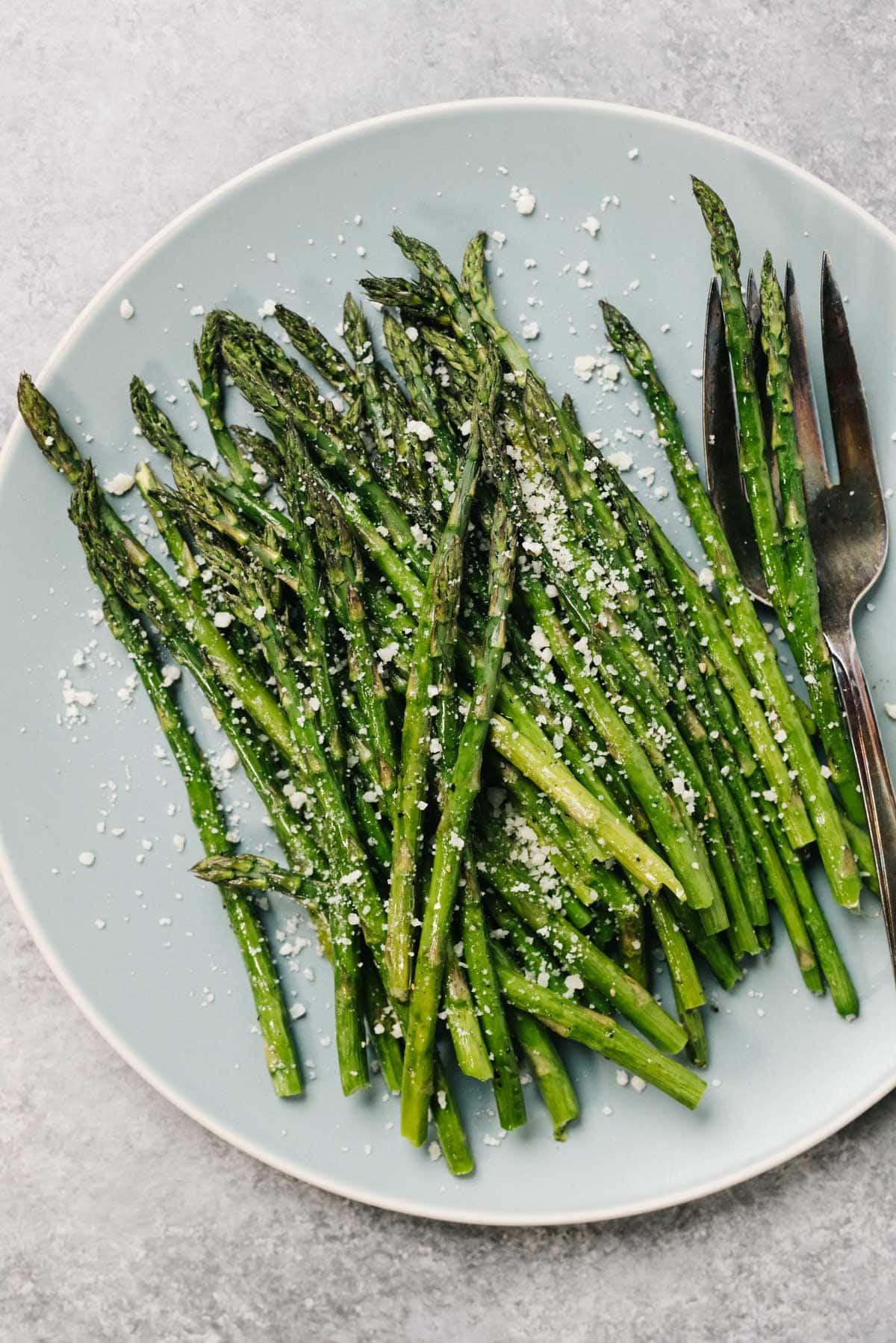 Roasted asparagus spears on a blue plate, garnished with grated parmesan cheese, with a silver serving fork.