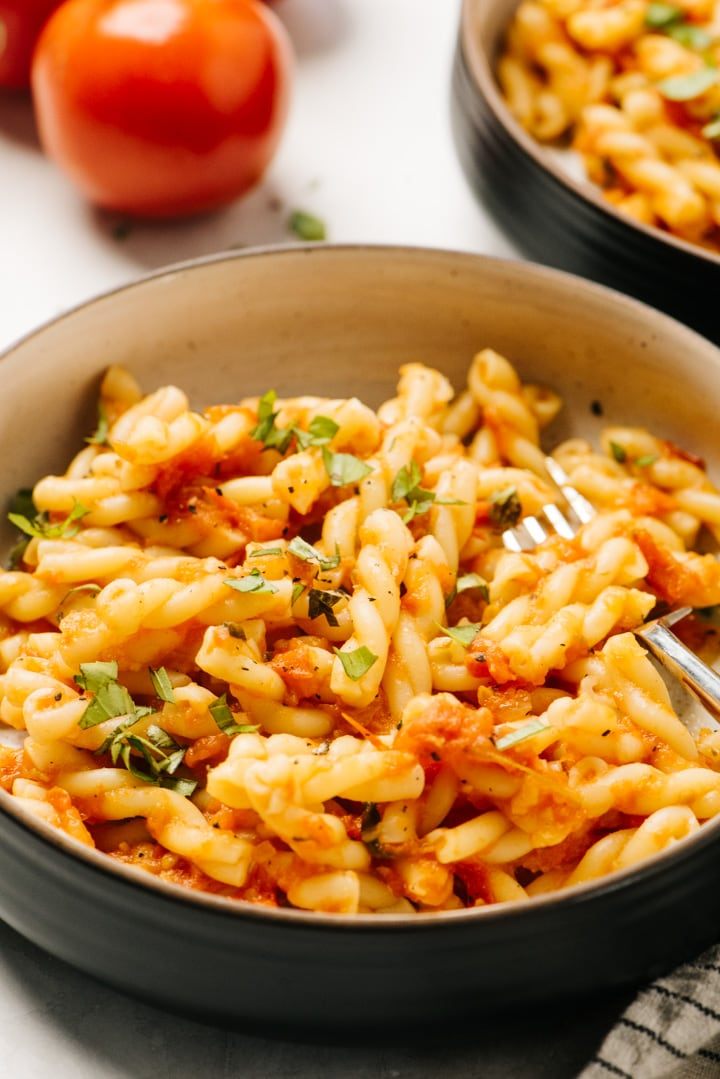 Side view, fresh tomato sauce tossed with pasta in a black and brown bowl with a silver fork.