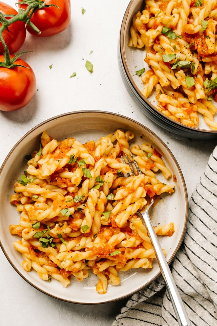 Two bowls of short pasta tossed with fresh homemade pasta sauce with ripe tomatoes and a striped linen napkin to the side.