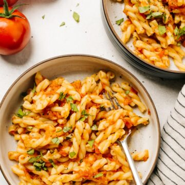 Two bowls of short pasta tossed with fresh tomato pasta sauce with ripe tomatoes and a striped linen napkin to the side.