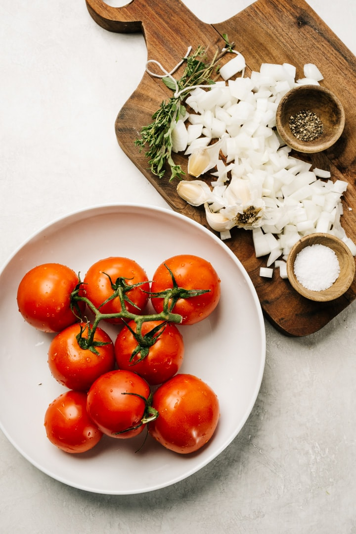 The ingredients for fresh tomato sauce using fresh tomatoes arranged on a cement background.