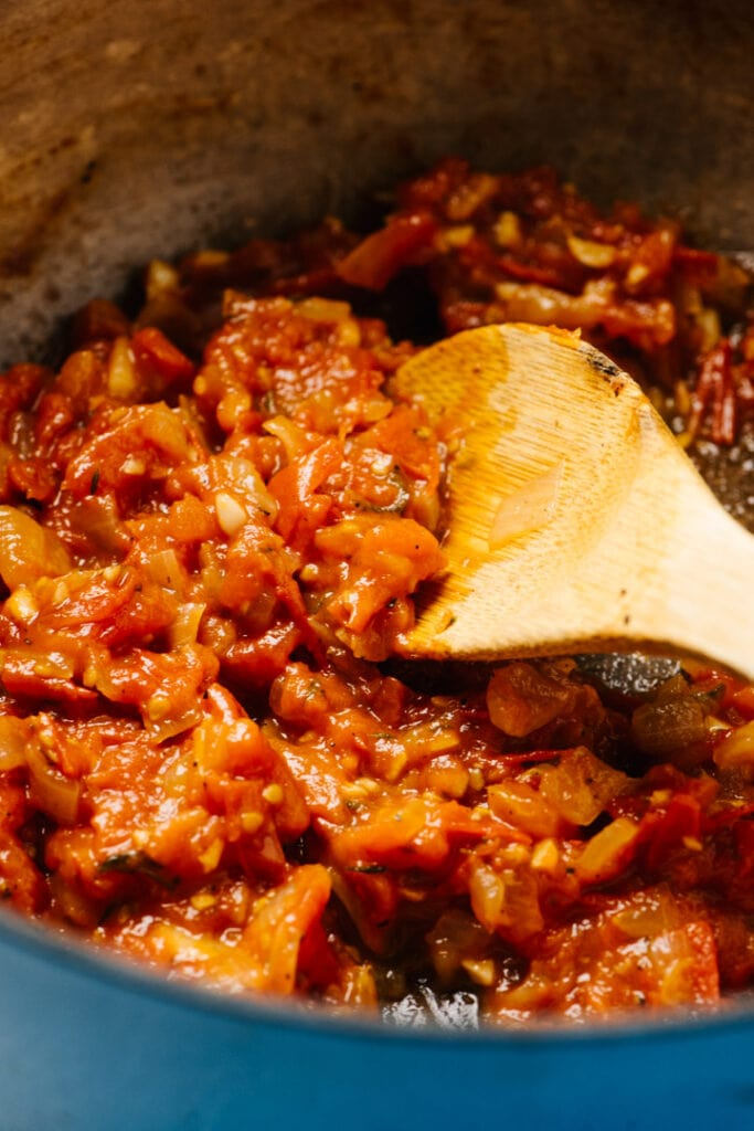 Side view, fresh tomato sauce in a dutch oven stirred with a wood spoon.
